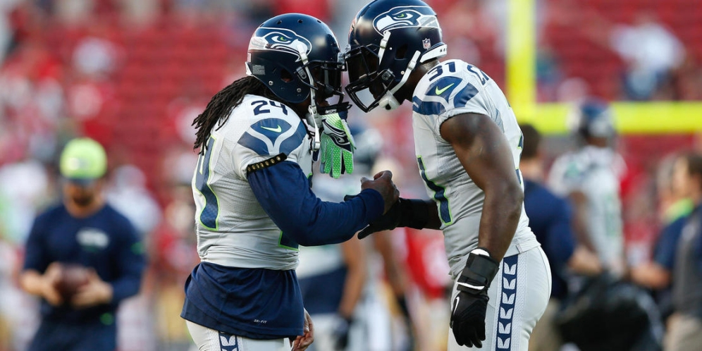 Seattle Seahawks running back Marshawn Lynch (24) speaks with safety Kam Chancellor (31) prior to an NFL football game against the San Francisco 49ers at Levi's Stadium on Thursday, October 22, 2015 in Santa Clara, Calif. Seattle won 20-3. (Aaron M. Sprecher via AP)
